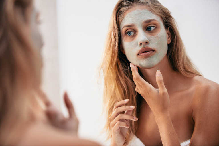 Блондинка с глиняной маской на лице.