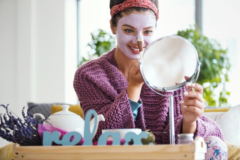 Перед зеркалом сидит девушка с маской на лице