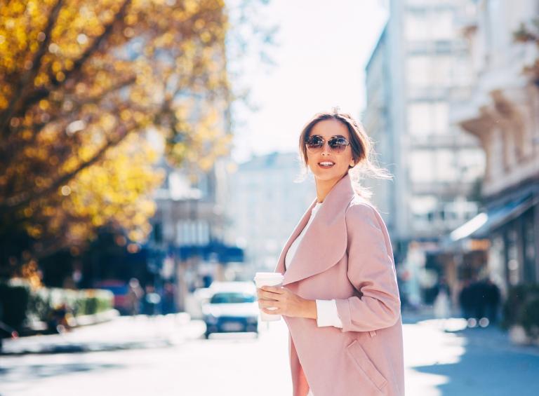 Молодая женщина в солнечных очках и розовом пальто на фоне городского пейзажа