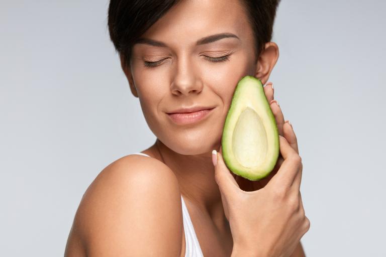 Брюнетка прижимает к лицу авокадо, обладающий питательными свойствами.