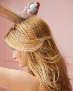 Девушка брызгает волосы лаком