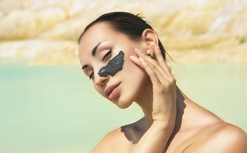 Девушка у моря с мазком чёрной глины на лице