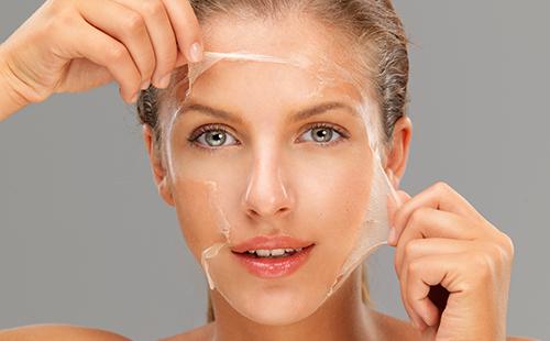 Красивая девушка снимает с лица плёночную маску