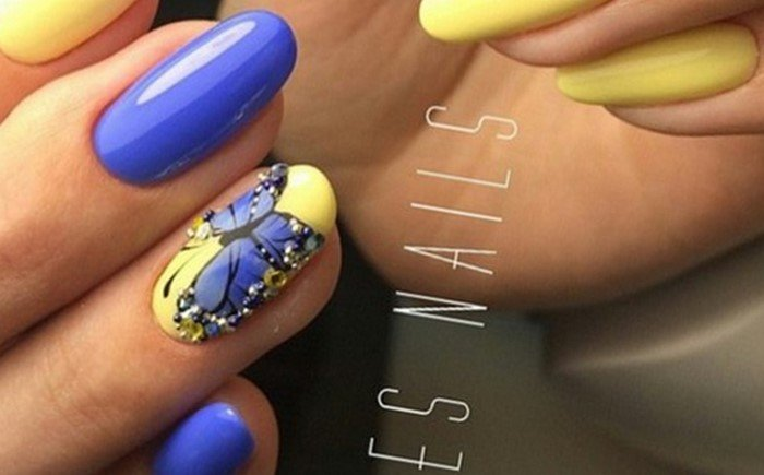 на желтых ногтях бабочка синяя и стразы