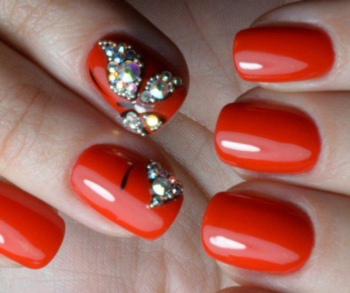 бабочка из страз на красных ногтях