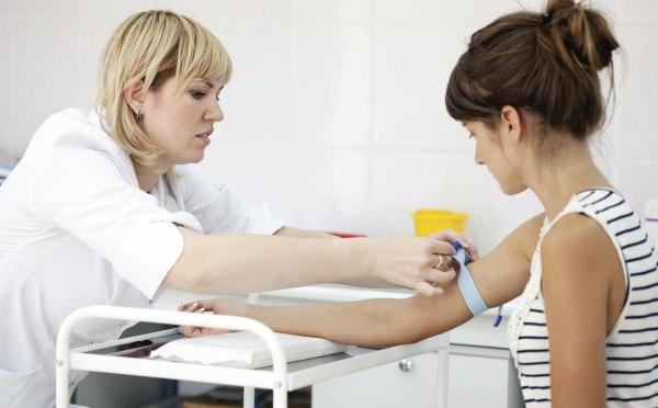 У девушки берут анализ крови.