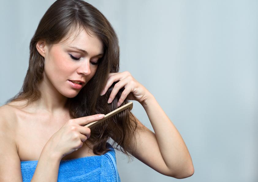 Attractive woman combing her hair