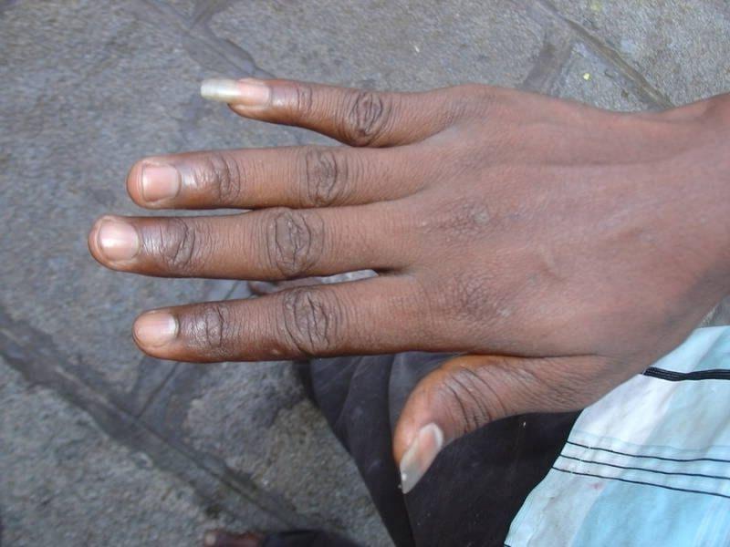 Рука темнокожего мужчины с отрощенными ногтями на мизинце и большом пальце